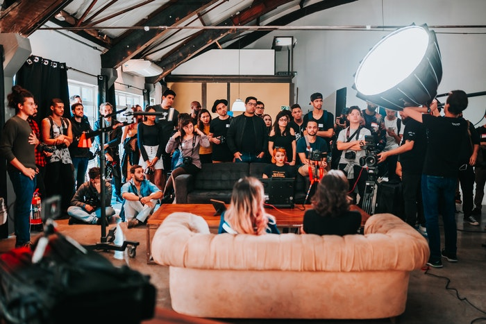 people watching a filmshoot with two people on a sofa and lighting to the side
