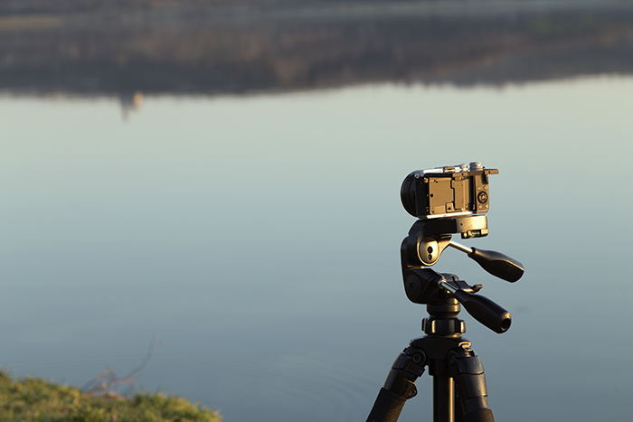 Camera on a tripod on the background of the lake.