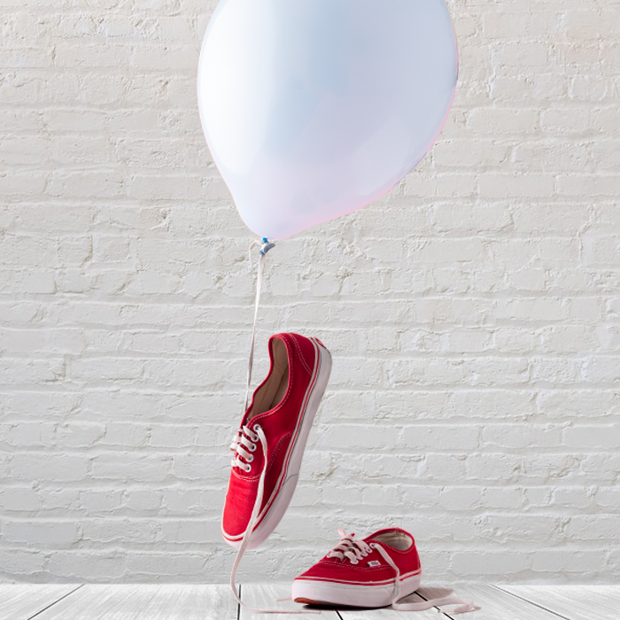 photo of red sneakers with a white balloon and a brick background