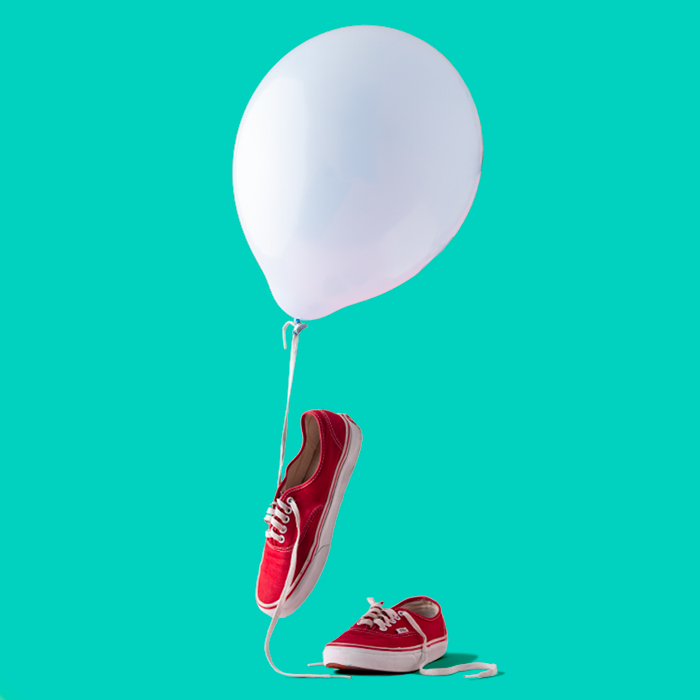 photo of red sneakers with a white balloon and a turquoise background