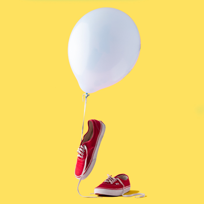 photo of red sneakers with a white balloon and yellow background