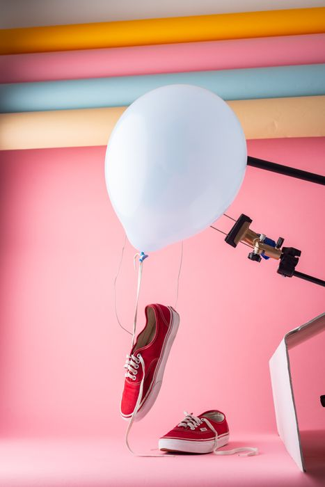 photo of red sneakers with a white balloon and pink background