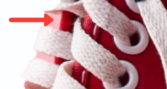 close-up photo of the shoelaces of a pair of red sneakers