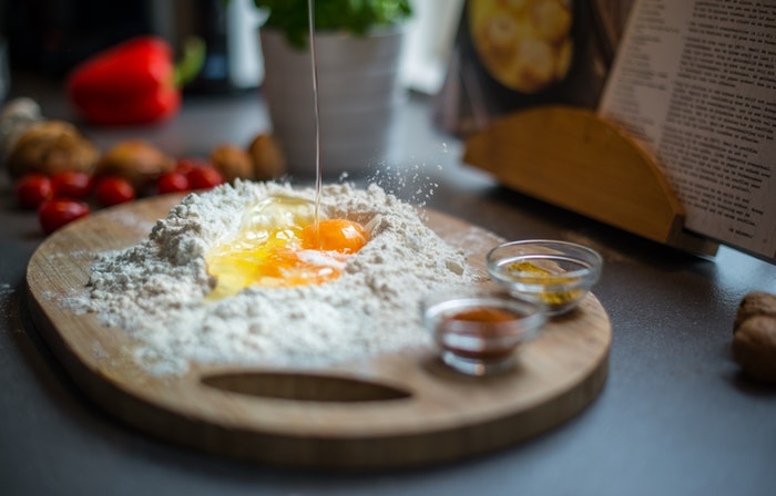 Eggs and flour on a wooden chopping board