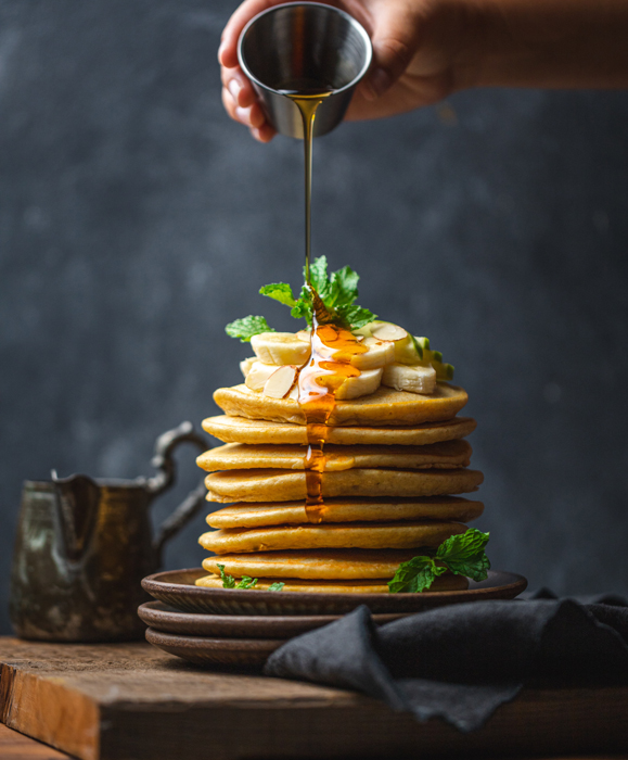 A hand pouring syrup on top of a stack of pancakes
