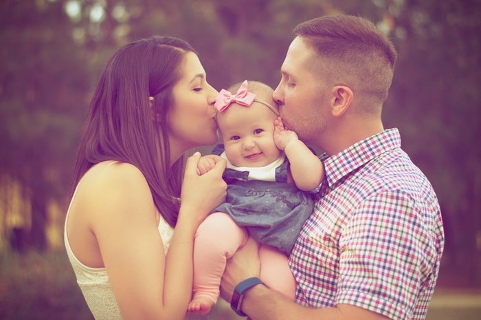 A couple kissing their baby