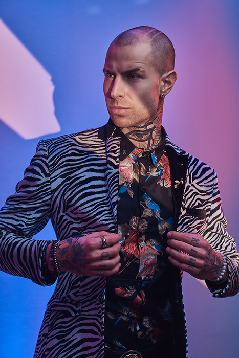 Expressive tattooed, bald fashionable male model posing in a studio for the photoshoot.