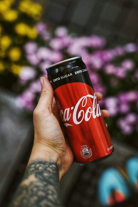 Uma foto de comida comercial de uma mão segurando uma Coca-Cola contra um fundo floral