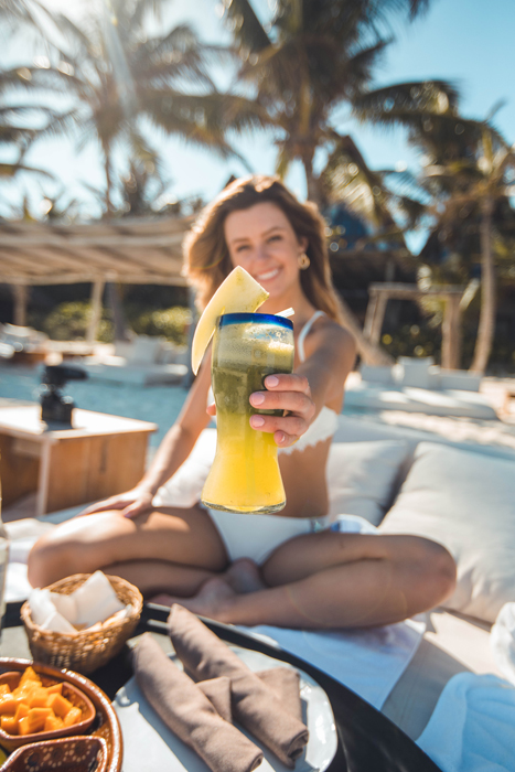 Uma menina segurando um cocktail tropical à beira da piscina