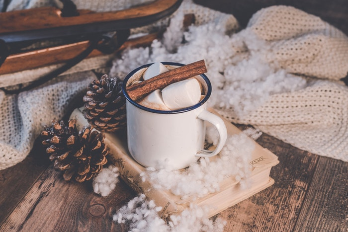 Someone drinking hot chocolate and reading under a warm blanket
