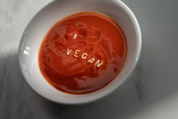 A soup with noodle spelling the word vegan