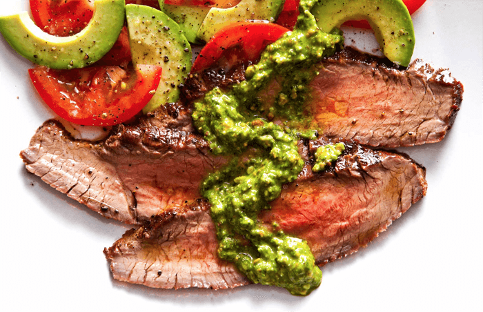 Delicious food photo of slices of meat with tomatoes and avocado