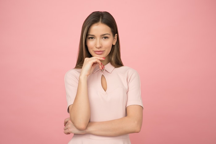 Woman in front of a pink background demonstrating a hand pose