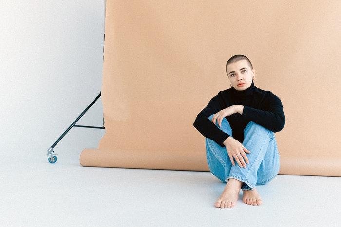 Femme assise devant un fond rose dans un studio photo à domicile