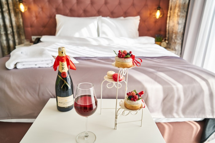Champagne and cakes at the foot of a lavish hotel bed