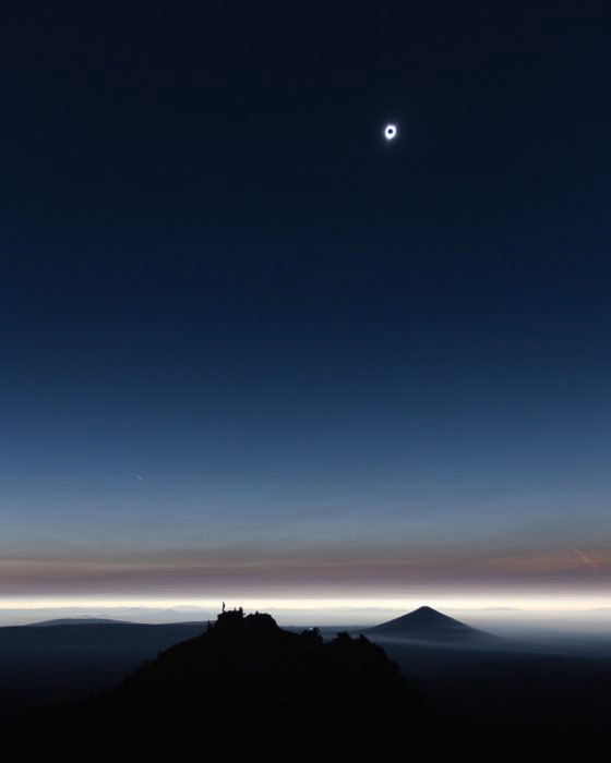photo of the solar eclipse over a landscape at night