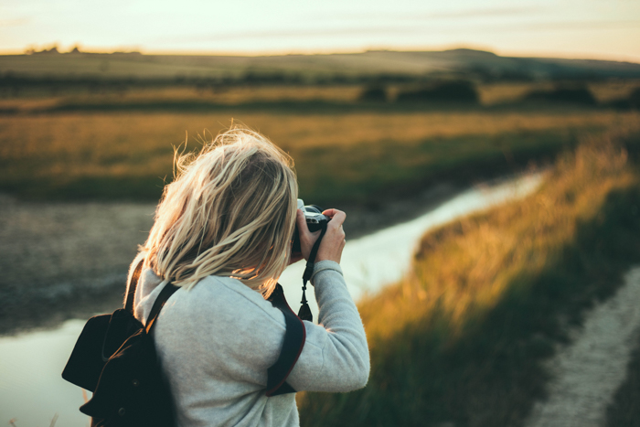 A girl taking a photo of a landscape
