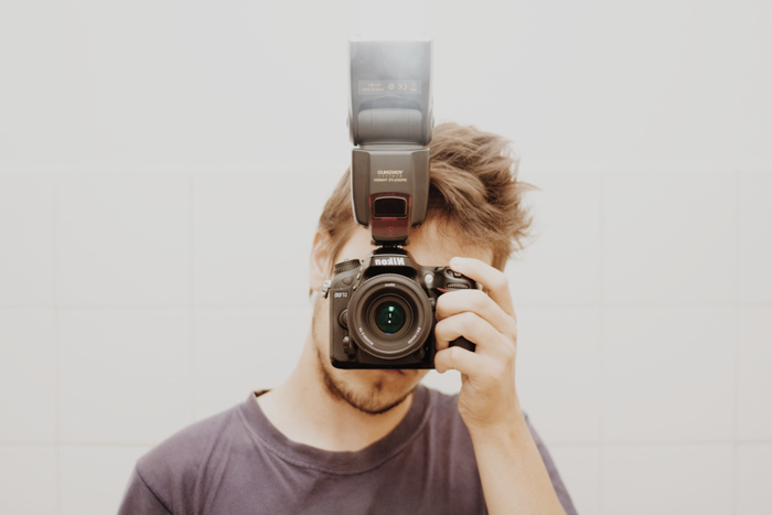 Photo of a guy holding a camera with external flash in front of his face