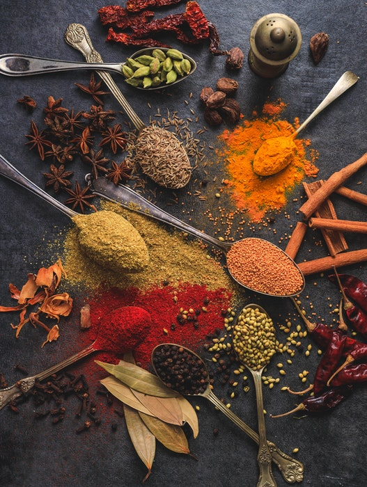 Indian food photography with spoons and spices scattered on a table