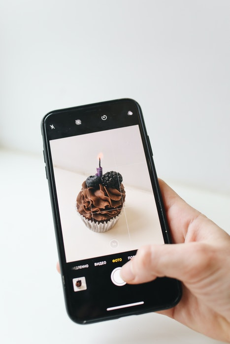 A person taking a photo of a chocolate muffin with an iphone camera
