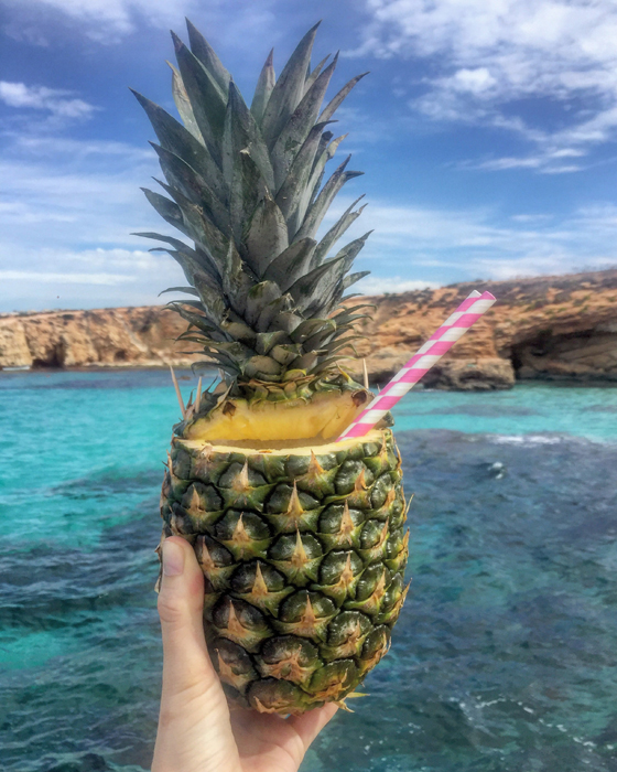 Cool iphone food photography of a hand holding a pineapple cocktail to a seascape