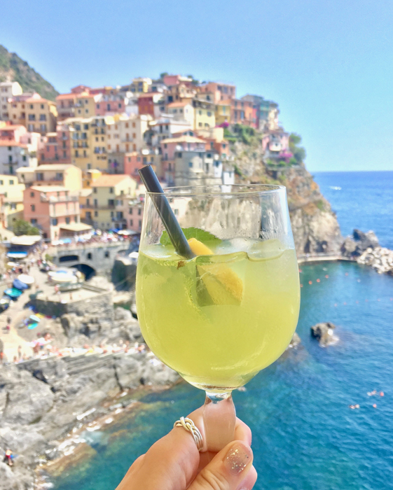A limoncello spritz held in front of a beautiful coastal town
