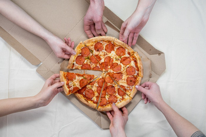 Overhead shot of people grabbing pizza slices from a box