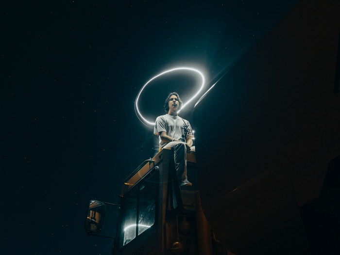 Man sitting on a truck with a halo in light graffiti above his head