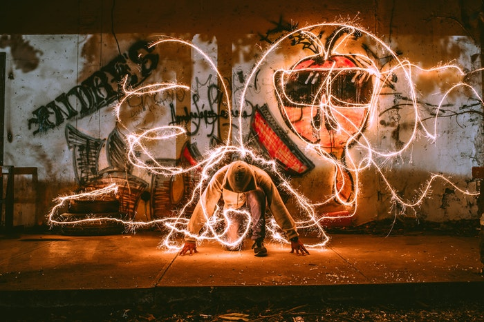 A man in front of a graffiti wall doing light painting