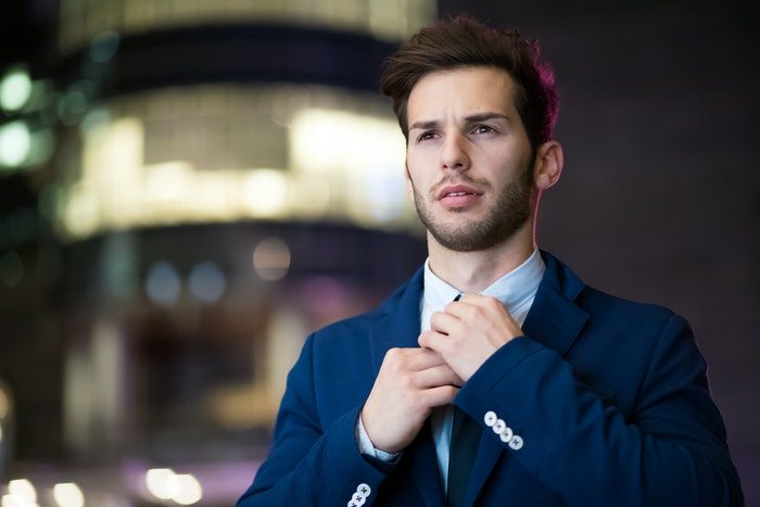 Male model buttoning his shirt collar