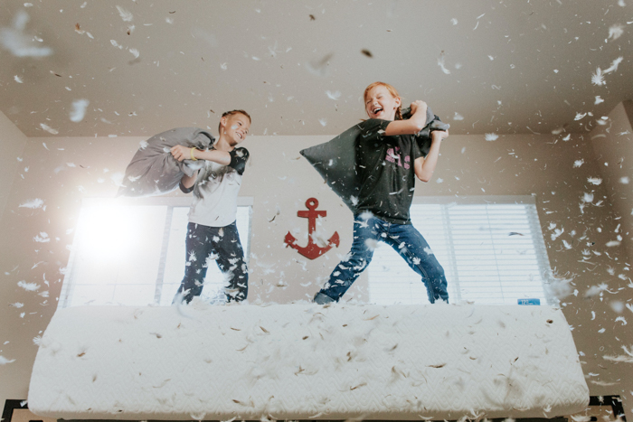 Two young kids having a pillow fight