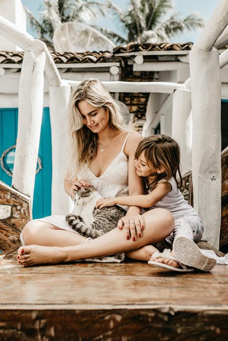Mãe e filha acariciando seu gato