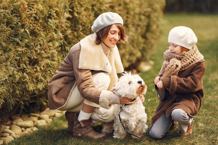 Mãe e filha acariciando seu cachorro ao ar livre