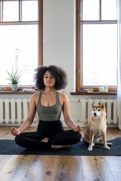 Uma garota fazendo yoga com seu cachorro fofo