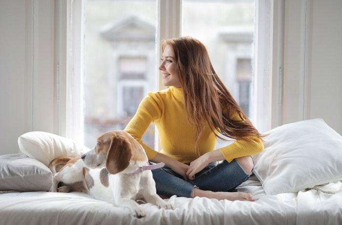 Uma menina sentada em uma cama com um cachorro