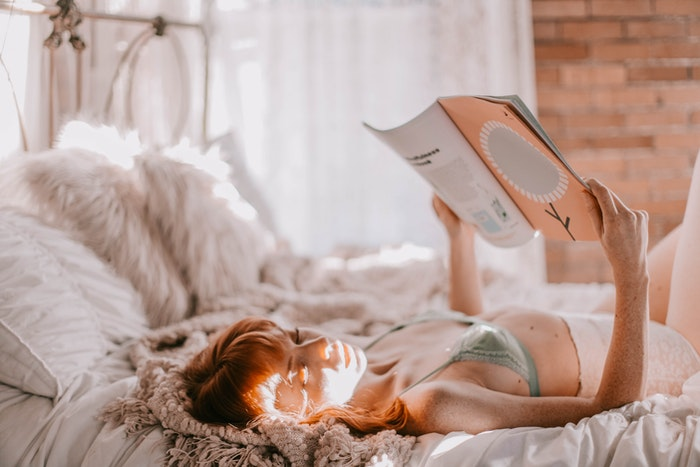 Woman laying on a bed and reading a book
