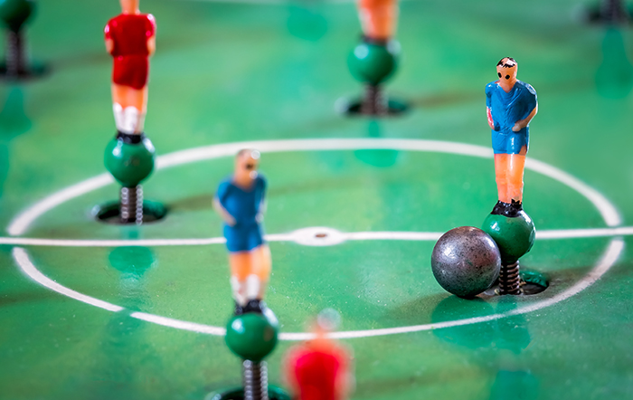Close-up shot of players figures of a foosball game.