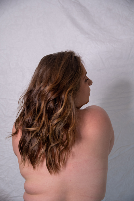 A plus size model poses for boudoir photography