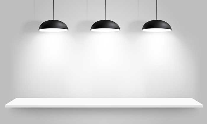 Three black lamps hanging from the ceiling, and a white table under them.