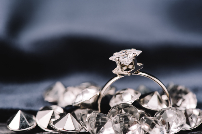 A diamond ring on dark background with other diamonds around it.