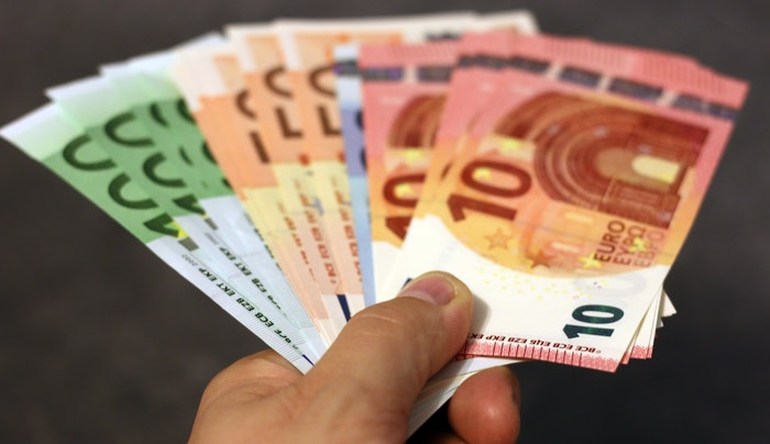 A hand holding a fan of euro notes
