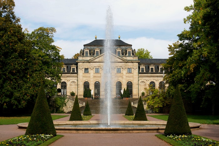 photo of a manor with a garden and a fountain in the foreground