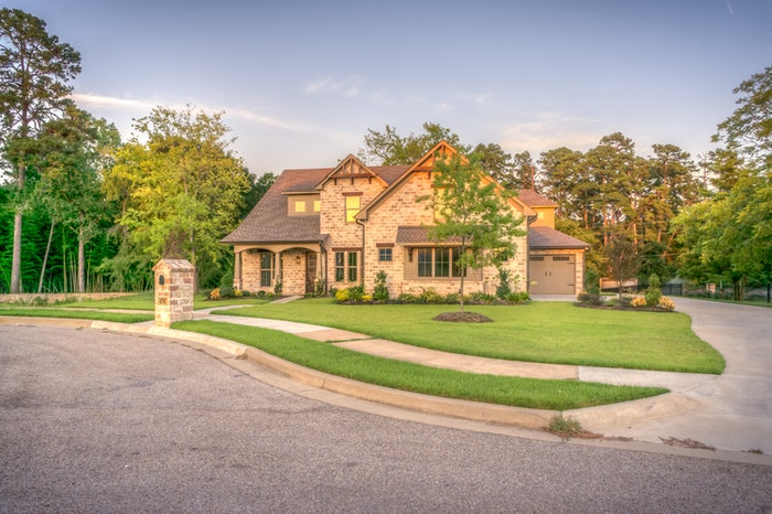 photo of a rustic style house with a green lawn