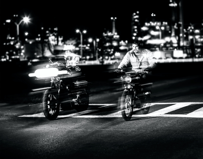 Black and white photo of two man on motorbikes with slow sync flash