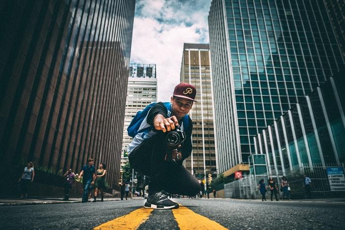 Man taking a photograph in an urban setting