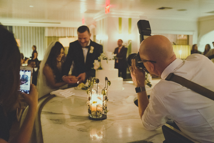 A wedding photographer taking a portrait of the happy couple cutting a cake