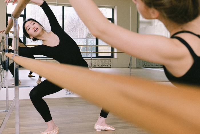 Woman in a black leotard doing ballet next to a mirror
