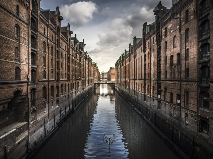 photo of a canal with brick buildings on both sides