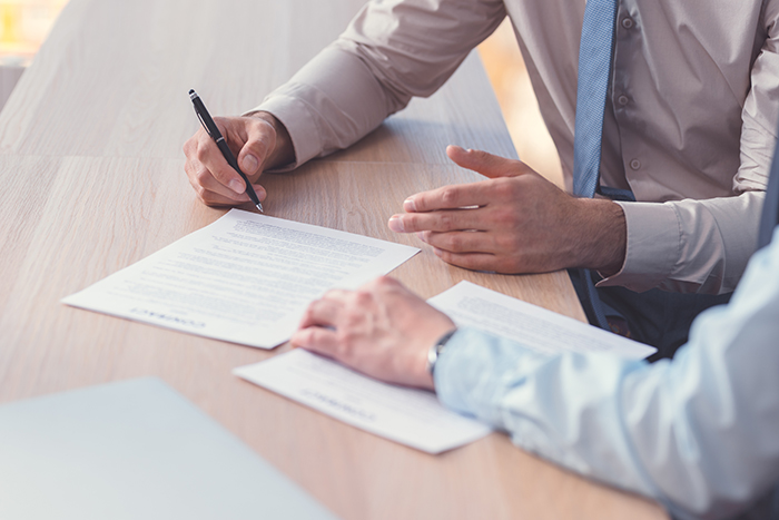 Business people signing a contract on a closeup image.