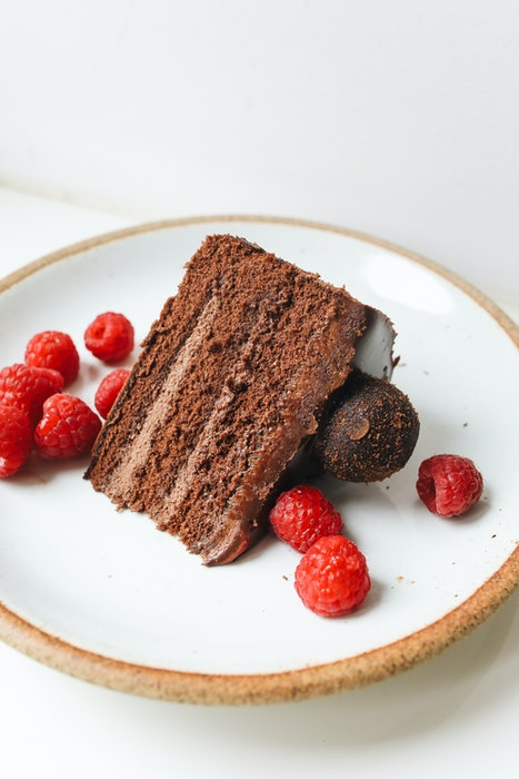 High angle photo of a delicious chocolate cake on a plate with berries